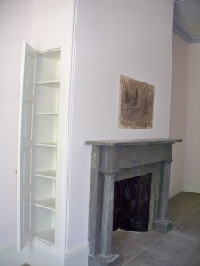 A marble mantle surrounds this fireplace featuring a cast iron fireback.